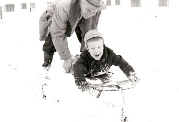 John is taking Johnny for a sledding lesson.