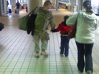 Soldier holding his son's hand walking through the Pittsburgh airport