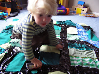 Alex zooms his lorry around the playmat