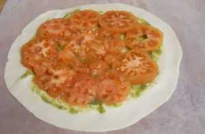Sobre el hojaldre poner pesto y los tomates.