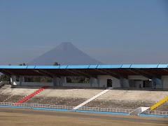 El palco del Estadio con una vista impresionante del volcan al fondo en la ciudad de Guatemala