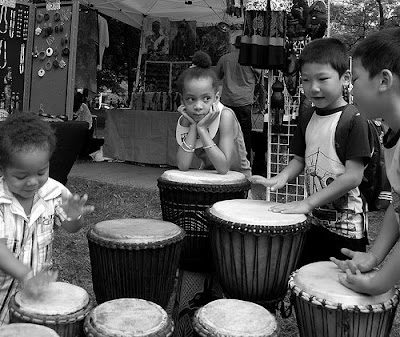 Canadian Children standing by and playing many djembes