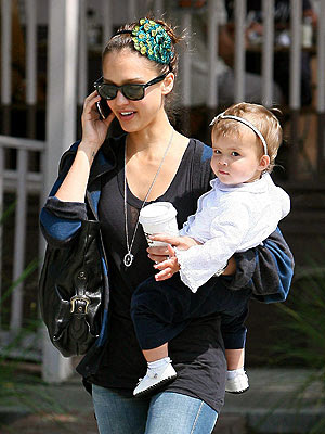 Jessica Alba carries her 11-month-old daughter Honor whilst catching up on