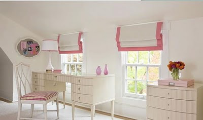 This bedroom has white blinds with an elegant pink trim boarder which matcheds the checked fabric on the bedroom chair.