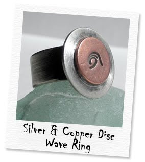 silver and copper disc wave logo ring