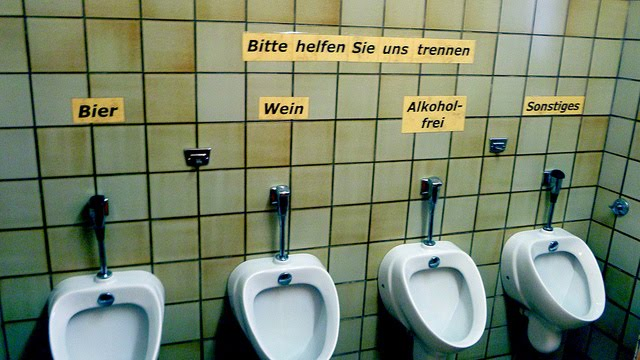 Writer Cory Doctorow was in a German restaurant when he saw these signs  above the urinals in a restroom  The top sign reads   Please help us  separate. Ultra Gross  German Urinal Humor