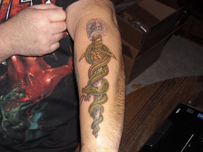 Skull snake and dagger tattoo.