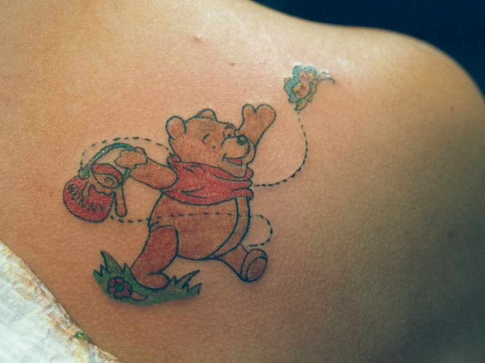 Winnie The Pooh and butterfly tattoo.