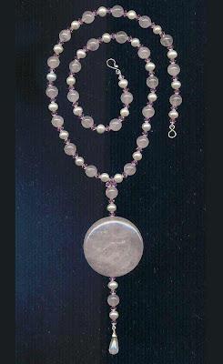 Colar de esferas de quartzo rosa e pérolas, intercaladas por cristais bicones Swarovski na cor light rose com um pingente no formato de moeda de 4cm de diâmetro de quartzo rosa