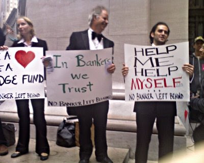 No Banker Left Behind street theater photo. Signs that say Help Me Help Myself and In Bankers We Trust