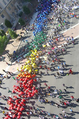people marching with colored umbrellas that made a rainbow flag pattern from above