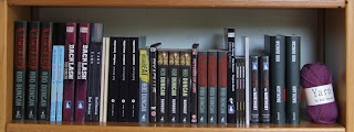 Rod Duncan books and DVDs collected on a wooden book shelf