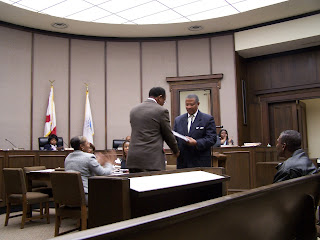 Outgoing Mayor James Perkins accepts a plaque in recognition of service to the city from Council President, and Mayor-elect, George Evans