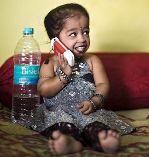 Jyoti with her cellphone. All her clothes has been custom made special for her because she cant get in store
