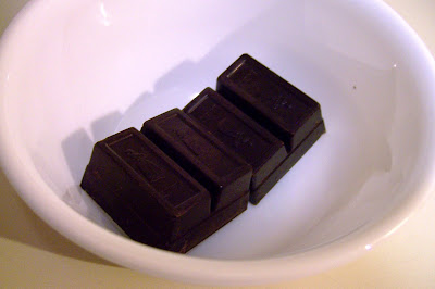 Two square of bakers chocolate in white bowl