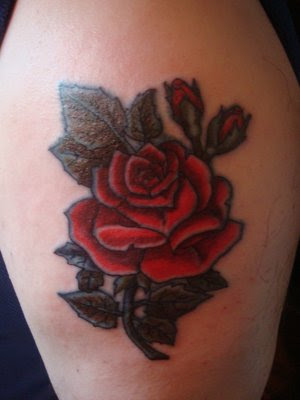 guns n roses tattoos. Black tribal dragon and red rose tattoo on the body.