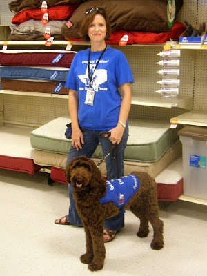 Alfie in his blue jacket & me in my blue puppyraiser shirt to match; we're in a pet store, standing in front of a bunch of dog beds...and yes, I was really in there to get him a bone!