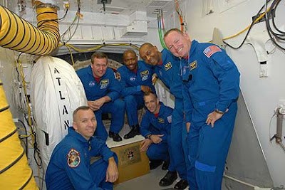 The STS-129 crew pose for a group portrait in the White Room at Launch Pad 39A at NASA's Kennedy Space Center in Florida