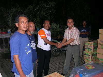 Mr. Ketut (right), on behalf of DEJAVATO Indonesia, gives the relief goods to Mr. Widodo as the coordinator of Kemudo village aid workers - Dejavato Indonesia