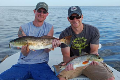 two young men with redfish