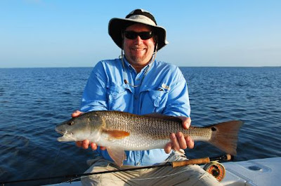 fisherman with redfish on fly rod