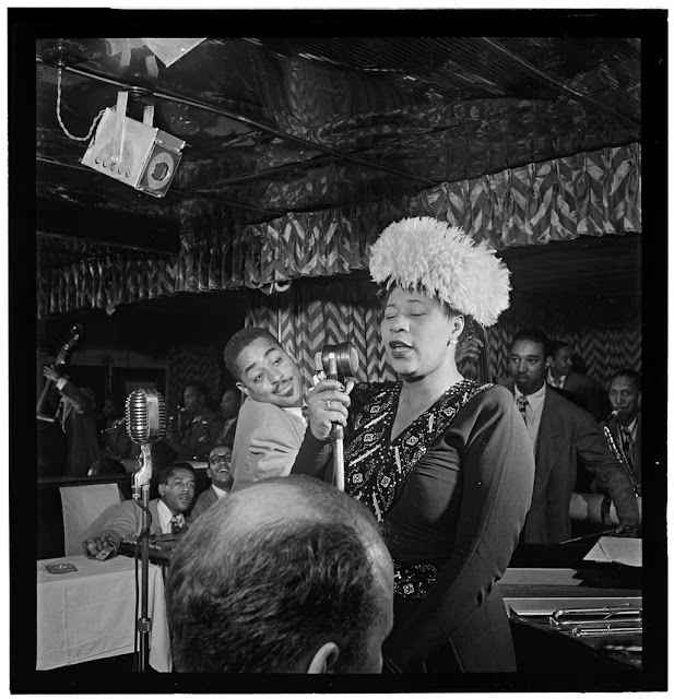 "Portrait of Ella Fitzgerald, Dizzy Gillespie, Ray Brown, Milt (Milton) Jackson, and Timmie Rosenkrantz, Downbeat, New York, N.Y., ca. Sept. 1947. Caption from Down Beat: An impressive photo of a truly impressive singer Ella Fitzgerald at the Downbeat, with Dizzy Gillespie making like a faun in the background. Dizzy has gone on his own way, while Ella is still keeping the club on the beat. Forms part of: William P. Gottlieb Collection (Library of Congress). In: ""Ella keeps it on the beat,"" Down Beat, v. 14, no. 20 (Sept. 24, 1947), p. 5."