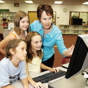 picture of children and a teacher at a computer