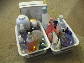 2 small plastic baskets filled with perfumes, lotions and powders