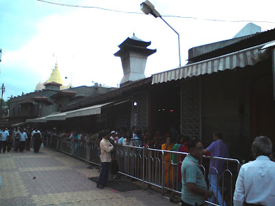 Long Queue for Dwarkamai Temple darshan in Shirdi, the golden spire of the Samadhi Temple in the background