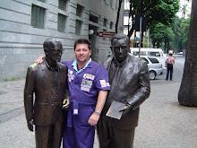 Piassa entre as escultura dos escritores Carlos Drummond de Andrade e Pedro Nava.