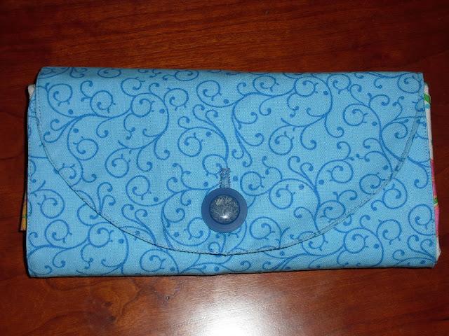 Cartera de tela azul que contiene una bolsa de tela plegada.
