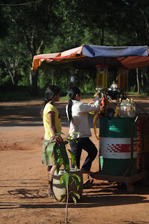 Two girls load gas into bottles. These mini gas stations are meant for people with motorbikes.