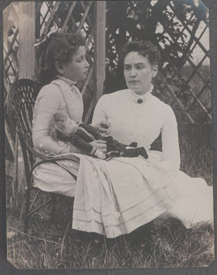 photo of 8 year old Helen Keller, holding a doll and sitting next to her teacher Anne Sullivan