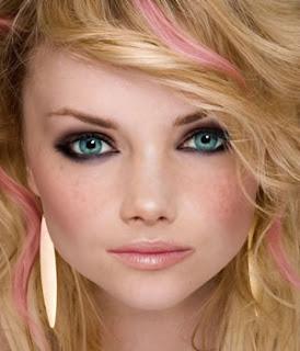 Szőke göndörödő hullámos hosszú haj, bájos mosolygós arc, és azok az égszínkék szemek