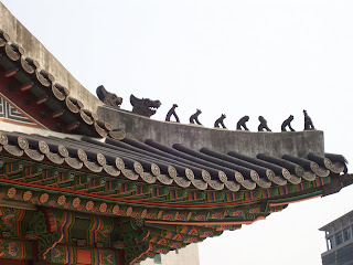 A colorful corner of a palace roof, with animal sculptures along its edge