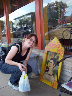Amber with a painting of Frida Kahlo outside on the street