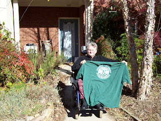 Eleanor Smith holding up a green ADAPT t-shirt in front of a condo house with autumn leaves on the sidewalk