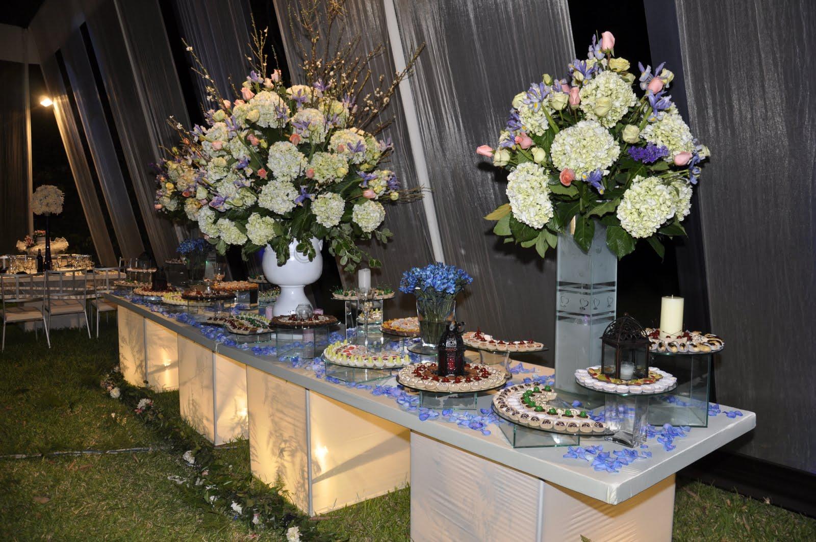 Mesa De Finos Dulces Decorado Con Grandes Arreglos De Flores Y Velas