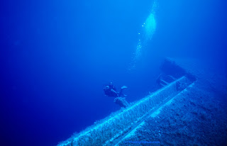 Diver swimming near a shipwreck