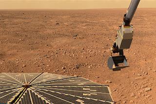 Fotografía de la sonda Phoenix, cargando suelo marciano en la pala de su brazo robótico