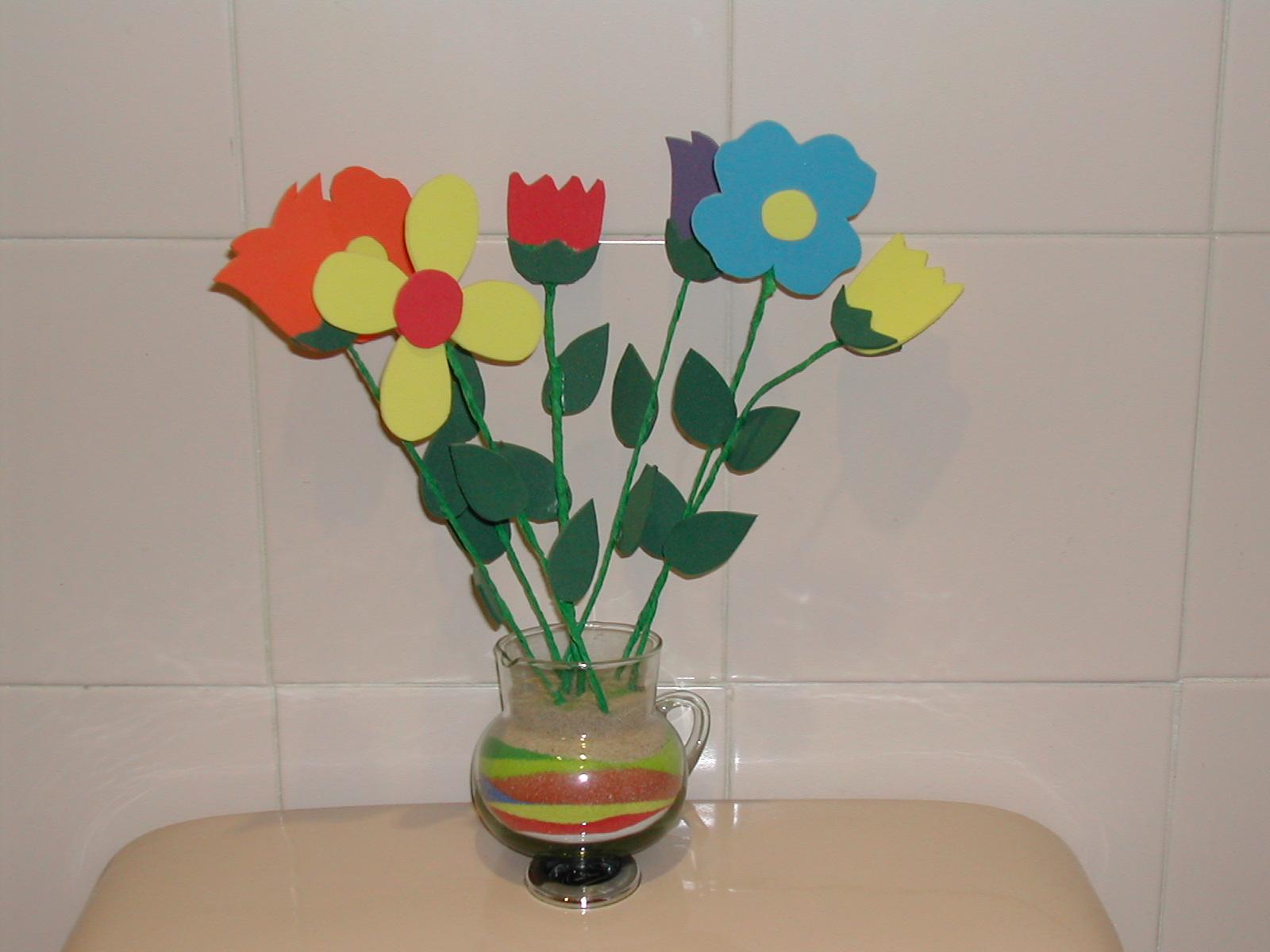 adornado con arenas de colores y con flores hechas de goma eva
