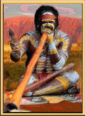Australian Aborigine playing a dijiridu with Uluru (Ayers Rock) in background.
