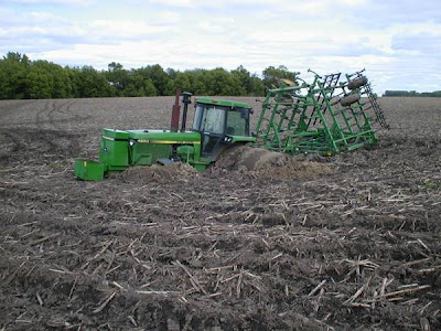 Photo of John Deere tractor stuck in a muddy field.