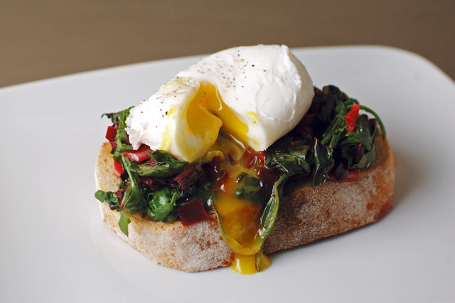 Lovely poached egg with arugula and beet greens on toasted french bread