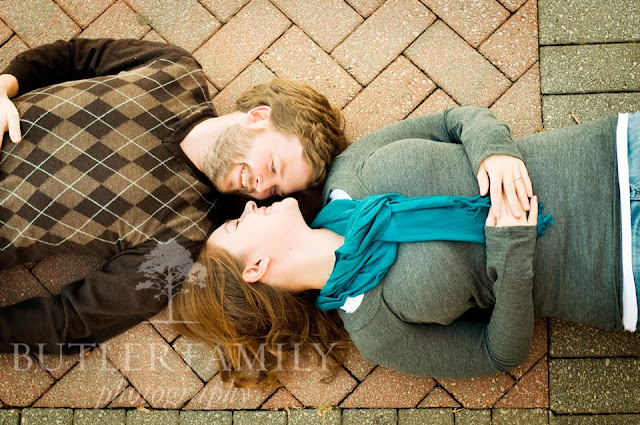 Bird's eye view portrait of the couple laying on brickwork and looking at eachother