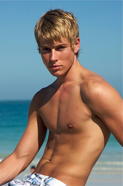 lovely blond boy sitting shirtless on the beach
