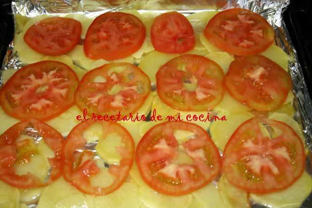 merluza al horno con cama de patatas y tomate