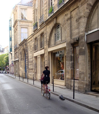 Parisienne on a bike in her black dress