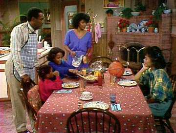The Cosby Family sit down and eat a meal.