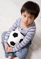 Photo of Ted as a boy with a ball